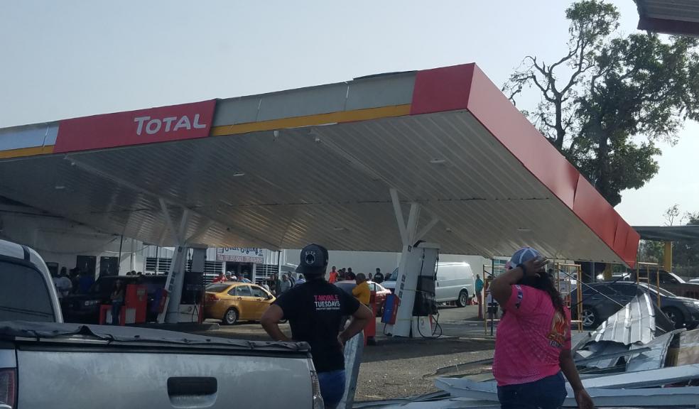 Ciudadanos se abastecen de combustible en una estación de Juana Díaz cuyo techo colapsó parcialmente tras el paso del huracán María.
