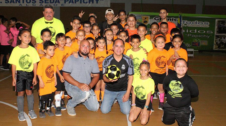 Peter Santiago Vega, director de Recreación y Deportes del Municipio de Guánica y el alcalde Santos Seda Nazario junto a un grupo de niños participantes en el torneo de fútbol sala. (Suministrada)