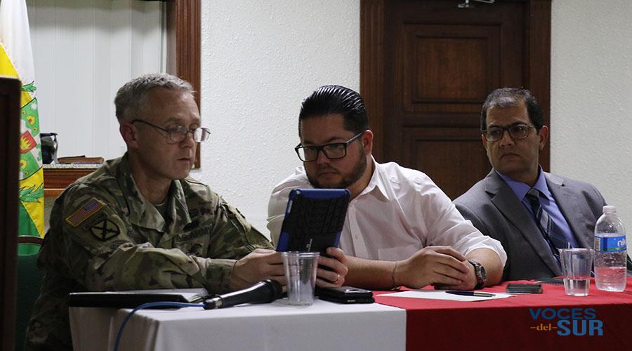 El coronel Aaron Reisinger y el alcalde Nelson Torres Yordán observan fotos de los daños provocados por el desbordamiento del Río Guayanilla.