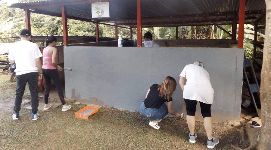 Los estudiantes limpiaron y pintaron los alrededores para mejorar la apariencia del hogar. (Suministrada)