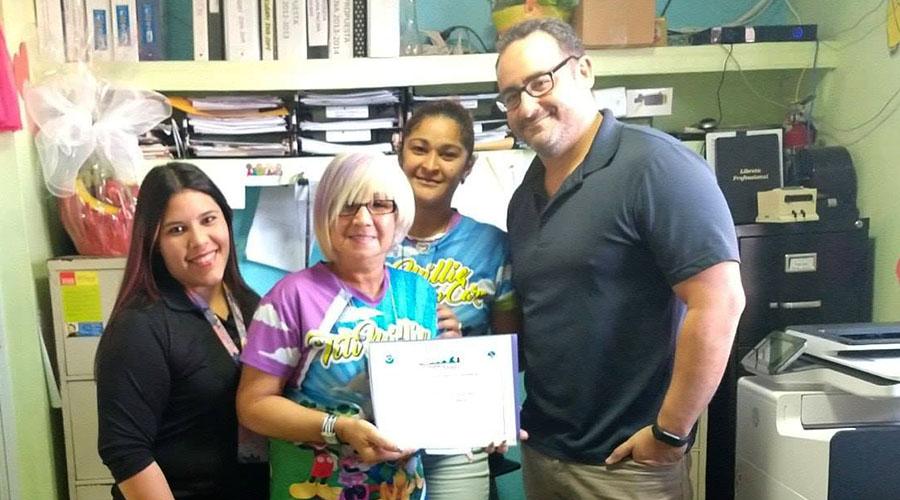 Ernesto Morales, del Servicio Nacional de Meteorología, entregó la certificación a Milagros Padró Vega, propietaria del centro. (Facebook / Red Sísmica de Puerto Rico)